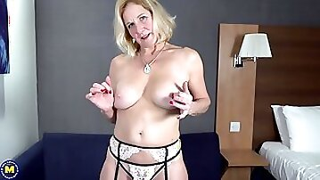 Busty, blonde granny in erotic stockings and garter belt is masturbating with a glass dildo