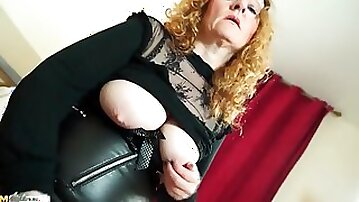 Slutty leather and fishnets on a mature redhead